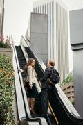 Businesswoman and man moving up escalator, Los Angeles, USA Stock Photos