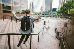 Businessman sliding down stair handrail, Los Angeles, USA Stock Photos