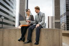 Businessman and woman sitting on wall using laptop, Los Angeles, USA - stock photo