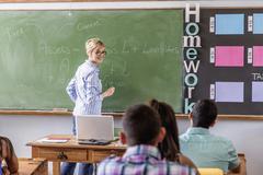 Female teacher addressing students in classroom - stock photo