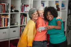 Portrait of three mature women, taking self portrait, using smartphone Stock Photos