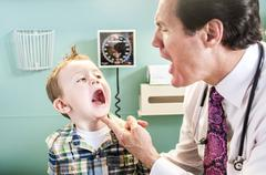 Young boy having check-up in doctor's office, doctor looking in boy's mouth Stock Photos