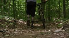 Mountain biker walking cycle down a trail - stock footage