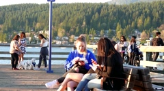 Two friends sitting and using cellphone on the bench at Rocky point park in P Stock Footage