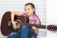 Little girl sitting with a guitar Stock Photos