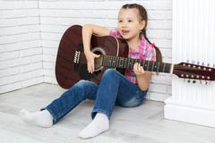 Little girl playing the guitar and singing Stock Photos
