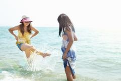 Mid adult woman and daughter splashing in sea, Zhuhai, Guangdong, China Stock Photos