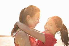 Mid adult woman and daughter hugging on beach, Zhuhai, Guangdong, China - stock photo