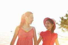 Mid adult woman and daughter strolling on beach, Zhuhai, Guangdong, China Stock Photos