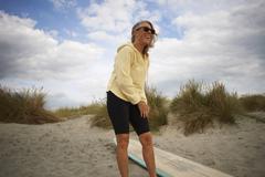 Senior woman putting on wetsuit - stock photo