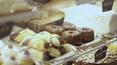View of pastry case panning to  young couple talking Stock Footage