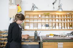 Female printer selecting letterpress letters in print workshop Stock Photos