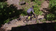 Tilt down from beautiful vista down to mountain biker on a trail Stock Footage