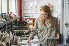 Female print designer examining designs in workshop - stock photo