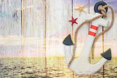 Double exposure: anchor and sunset in the ocean Stock Photos