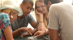 Four multiethnic friends are plannig a trip in summer day Stock Footage