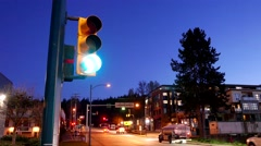 City traffic light turns from green to red with driving car in city at night - stock footage