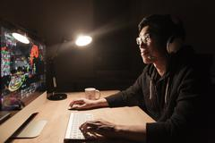 Happy male gamer playing computer game in dark room - stock photo