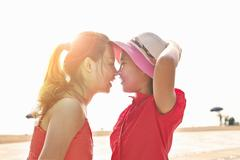 Mid adult woman and daughter face to face on beach, Zhuhai, Guangdong, China - stock photo