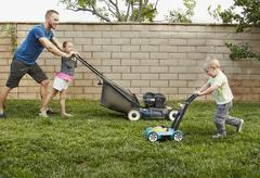 Family mowing lawn in backyard - stock photo