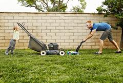Father and son mowing lawn in backyard Stock Photos