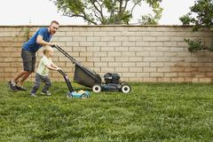 Father and son mowing lawn in backyard - stock photo