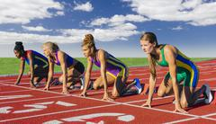 Four female athletes on athletics track, about to start race - stock photo