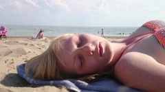 Young blond woman sunbathing on the beach Stock Footage