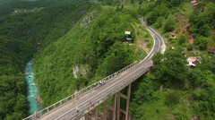 Durdevica bridge. Cars driving and people riding on zipline. Montenegro Stock Footage