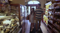 Young couple walking into pastry shop Stock Footage