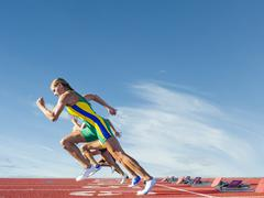 Three female athletes on athletics track, racing - stock photo