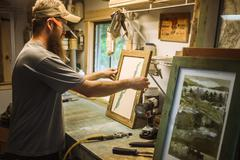 Artist working in workshop, framing artwork Stock Photos