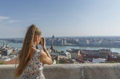 Mid adult woman taking photography of Buda from the Fisherman's Bastion, - stock photo