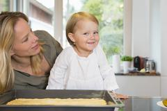 Portrait of female toddler and mother in kitchen Stock Photos