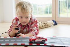 Boy playing with toy  racing car on living room floor - stock photo