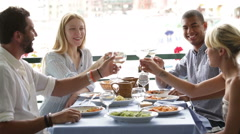 Four multiethnic friends are eating at italian restaurant in summer day Stock Footage