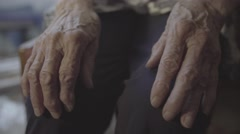wrinkled hands of an elderly woman on her knees - stock footage