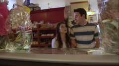 View from behind bakery counter of young couple Stock Footage
