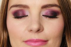 Woman closed eyes with violet dark shadows makeup - stock photo