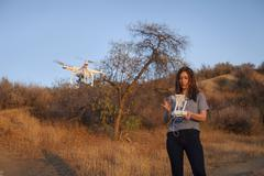 Female commercial operator on scrubland flying drone, looking down, Santa - stock photo