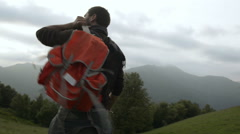 Young man with a red vintage backpack is walking outdoor on mountain path - stock footage