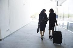 Two businesswomen in walkway, pulling suitcase, rear view - stock photo