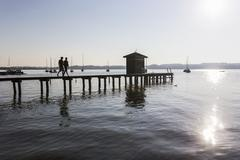 Silhouette of couple walking on pier at lake to boathouse, Schondorf, Ammersee, Stock Photos