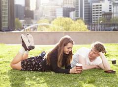 Young couple having coffee break on grass, Melbourne, Victoria, Australia Stock Photos