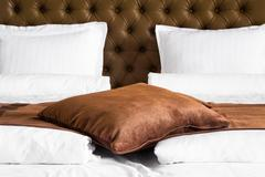 Brown cushion on a stylish double bed Stock Photos
