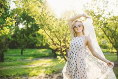 Young woman in orchard wearing sleeveless dress and sunglasses holding lace Stock Photos