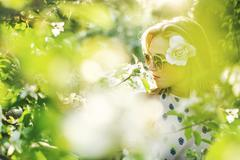 View through foliage of young woman, flower in hair, wearing nose stud and - stock photo