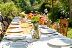 Table setting for large family at tomato eating festival - stock photo