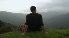 Young man on mountain with a red vintage backpack seated on grass - stock footage