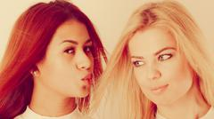 Blonde and mulatto girl together. - stock photo